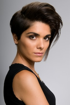 Mooie jonge vrouw met rechte korte haarstijl op grijze muur