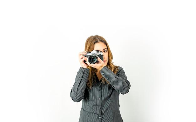 Mooie jonge vrouw met retro camera die onderwerp aanwijst en de focusring op de lens draait. vintage versus nieuwe fotografietechnologieën in de moderne tijd. grote kopie ruimte voor online fotocursussen adv