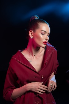 Mooie jonge vrouw met rode lippen en hoge staart in de mantel van bourgondië op zwart.