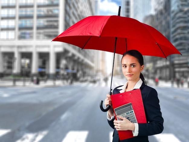 Mooie jonge vrouw met rode paraplu op straat van moderne stad