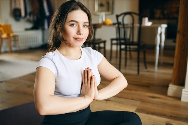 Mooie jonge vrouw met rond lichaam en blauwe ogen, zittend op de vloer, hand in hand tegen elkaar gedrukt, ontspannen gelaatsuitdrukking na meditatie hebben opgefrist