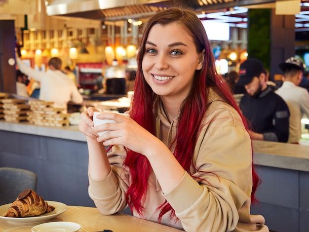 Mooie jonge vrouw met rood haar genieten van een kopje koffie met een croissant in een restaurant