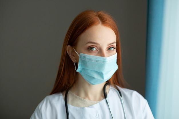 Mooie jonge vrouw met rood haar in een medische jurk en masker