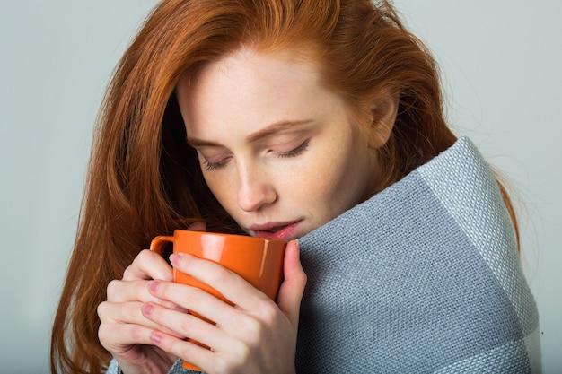 Mooie jonge vrouw met rood haar in een warme plaid met een mok hete thee