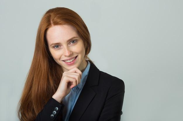 Mooie jonge vrouw met rood haar in een zwarte jas