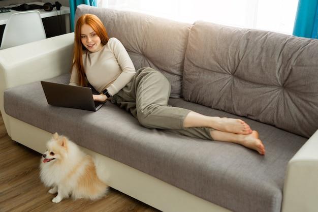 Mooie jonge vrouw met rood haar ligt thuis op de bank met een laptop