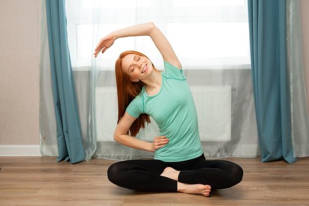 Mooie jonge vrouw met rood haar yoga thuis doen