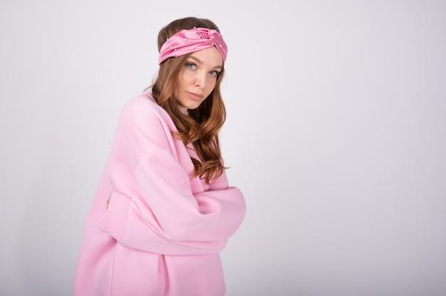Mooie jonge vrouw met rood krullend haar, losse roze sweatshirt dragen, modellering tegen witte muur