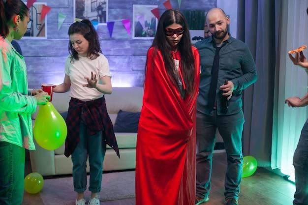 Mooie jonge vrouw met rood superheldenkostuum op vriendenfeest.