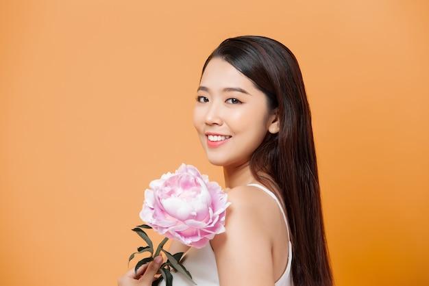 Mooie jonge vrouw met roze bloem geïsoleerd op geel