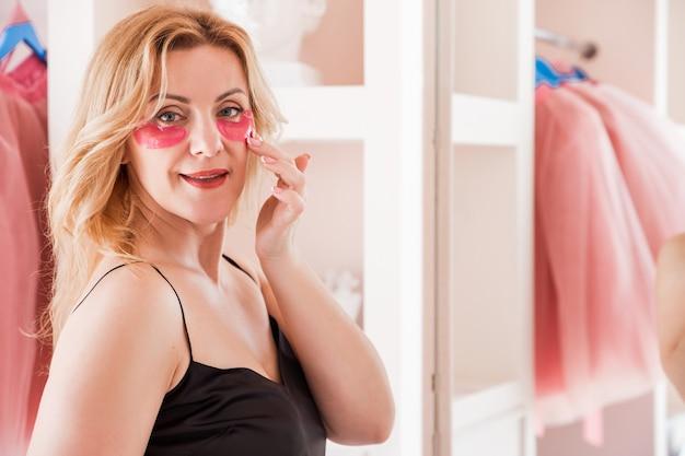Mooie jonge vrouw met roze vlekken onder haar ogen staat voor de spiegel in haar slaapkamer