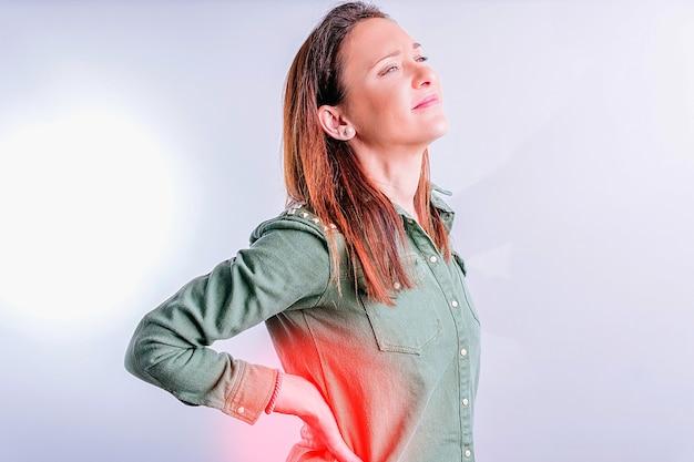 Mooie jonge vrouw met rugpijn in lumbale met rood gebied op witte achtergrond