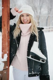 Mooie jonge vrouw met schaatsen, close-up