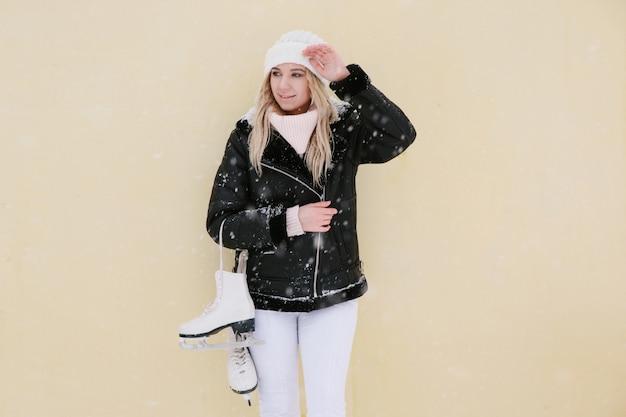 Mooie jonge vrouw met schaatsen, kopie ruimte