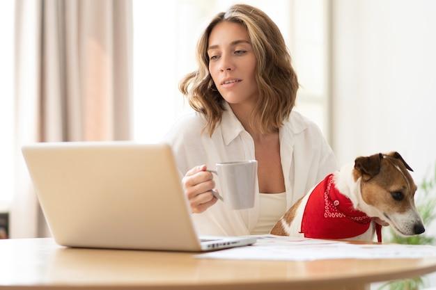 Mooie jonge vrouw met schattige hond die op laptop thuis werkt.