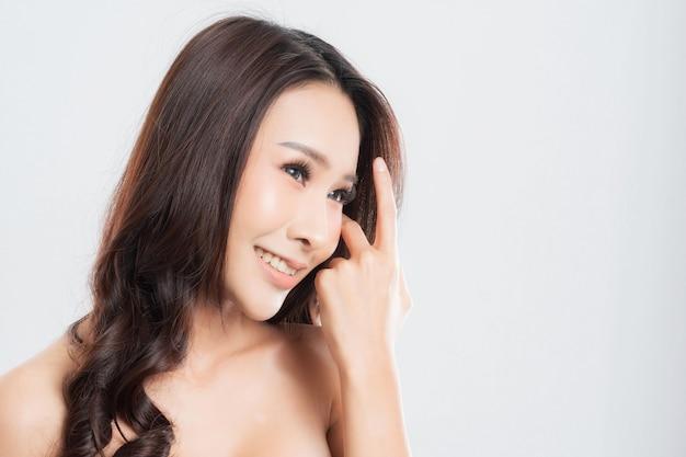 Mooie jonge vrouw met schone, frisse huid, haar glad, een product voorstellend. gebaren voor reclame op grijze achtergrond, vooraanzicht, met kopie ruimte.