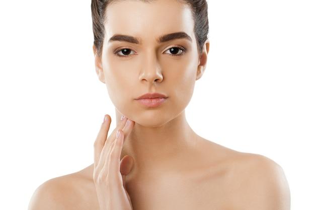 Mooie jonge vrouw met schone frisse huid raakt eigen gezicht aan. cosmetologie, schoonheid en spa.