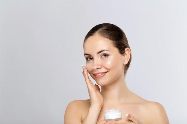 Mooie jonge vrouw met schone frisse huid raakt eigen gezicht aan. het meisje houdt en past vochtinbrengende room toe. gezichtsbehandeling. huidverzorging. cosmetologie, schoonheid en spa.