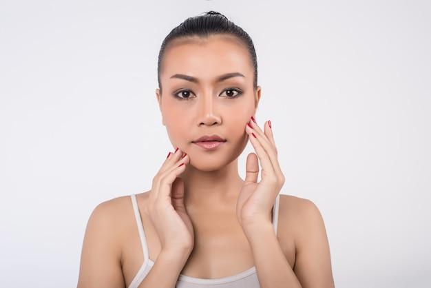 Mooie jonge vrouw met schone frisse huid touch eigen gezicht