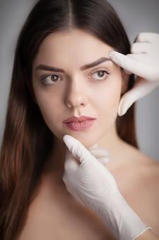 Mooie jonge vrouw met schone huid aanraking eigen gezicht. gezichtsbehandeling . cosmetologie, schoonheid en spa