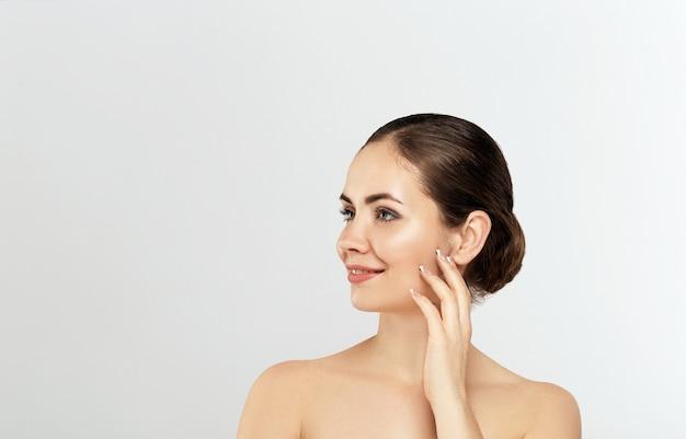 Mooie jonge vrouw met schone huid. gezichtsbehandeling. cosmetologie. schoonheid en spa. leuk en aantrekkelijk meisje met een prettige glimlach.