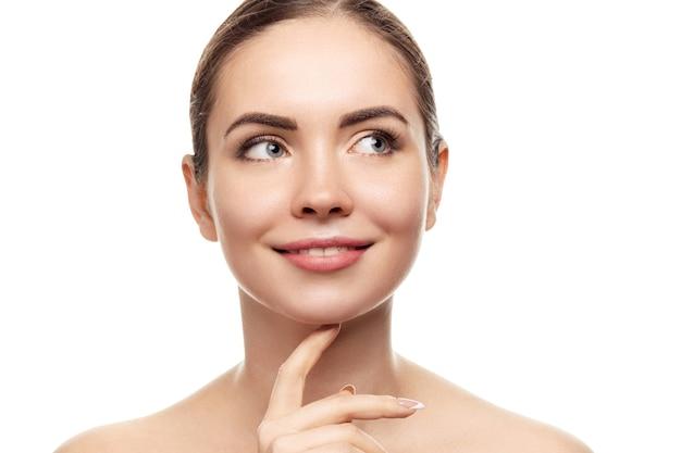 Mooie jonge vrouw met schone huid kijken weg. meisje schoonheid gezichtsverzorging. gezichtsbehandeling. huidsverzorging. cosmetologie, schoonheid en spa.