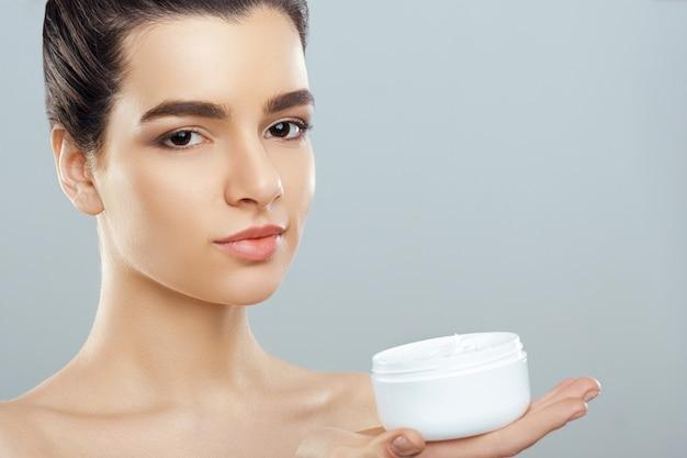 Mooie jonge vrouw met schone huid. meisje schoonheid gezichtsverzorging. cosmetologie, schoonheid en spa.