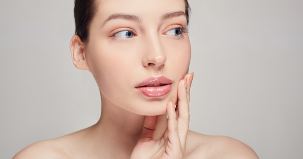 Mooie jonge vrouw met schone huid raakt haar eigen gezicht met haar hand