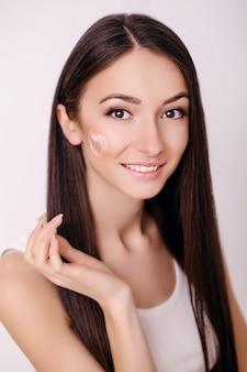 Mooie jonge vrouw met schone huid raakt haar gezicht. gezichtsbehandeling . cosmetologie, schoonheid en spa.