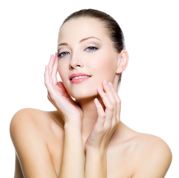 Mooie jonge vrouw met schone huid van het gezicht. vrij vrouwelijk poseren op witte achtergrond