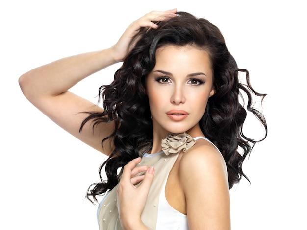 Mooie jonge vrouw met schoonheids lang krullend haar. mannequinportret op witte achtergrond wordt geïsoleerd die