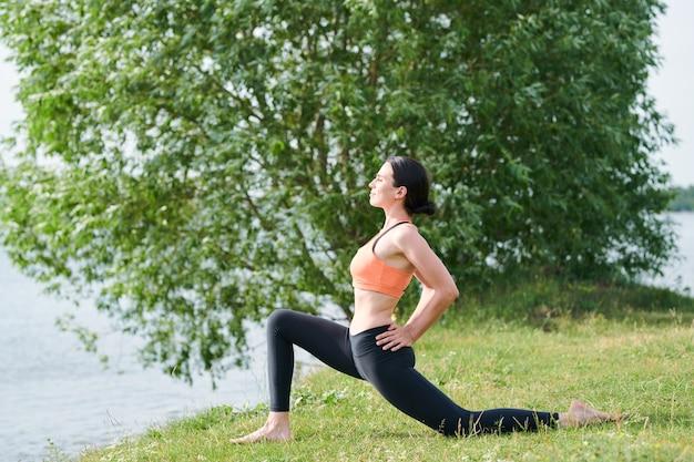Mooie jonge vrouw met slank lichaam die lage lunge poseert met de handen op de heupen tijdens het beoefenen van yoga op de wal