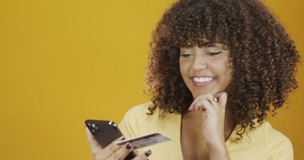 Mooie jonge vrouw met smartphone en creditcard. online winkelen transactie. mobiel bankieren cashless methode. glimlachend jong afrikaans amerikaans meisje op geeloranje muurachtergrond