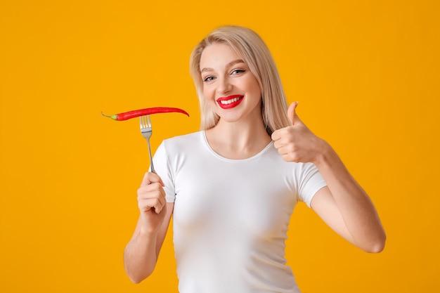 Mooie jonge vrouw met spaanse peperpeper die duim-omhoog toont op kleurenoppervlakte