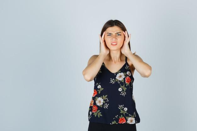 Mooie jonge vrouw met sterke hoofdpijn in blouse en op zoek geïrriteerd