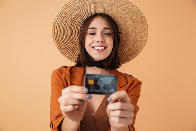 Mooie jonge vrouw met strohoed en zomeroutfit die geïsoleerd over een beige muur staat en een plastic creditcard toont