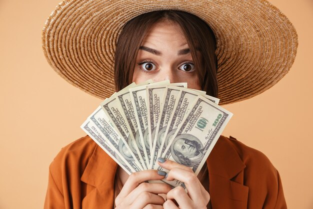 Mooie jonge vrouw met strohoed en zomeroutfit die geïsoleerd over een beige muur staat en geldbankbiljetten toont