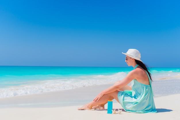 Mooie jonge vrouw met suncream die op tropisch strand ligt