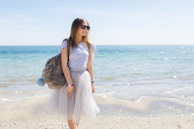 Mooie jonge vrouw met tas staat in de buurt van zee