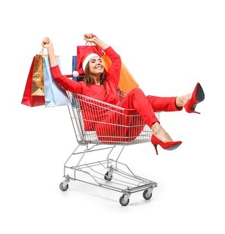 Mooie jonge vrouw met tassen zitten in winkelwagen