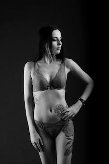 Mooie jonge vrouw met tatoeage in studio, mooi en verleidelijk.
