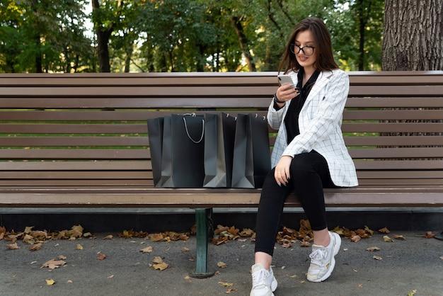 Mooie jonge vrouw met telefoon en boodschappentassen op de bank. online winkelen. kortingen, promoties, zwarte vrijdag.
