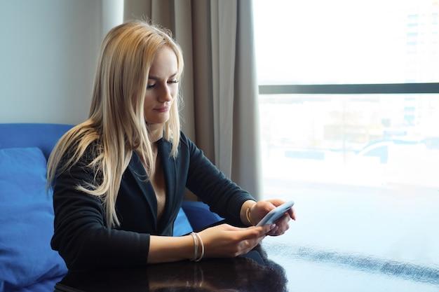 Mooie jonge vrouw met telefoon zittend aan een tafel in een café, kopieer ruimte