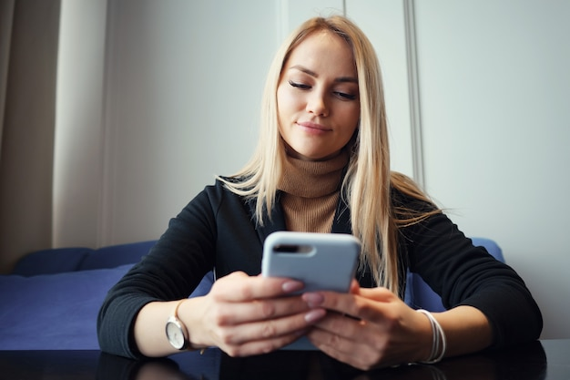 Mooie jonge vrouw met telefoon zittend aan een tafel in een café.