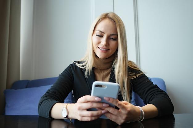 Mooie jonge vrouw met telefoon zittend aan een tafel in een café
