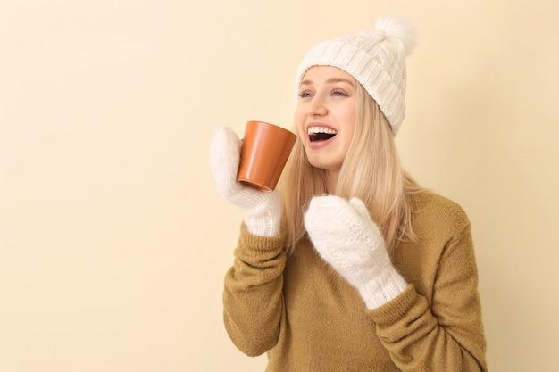 Mooie jonge vrouw met thee op kleurenoppervlak
