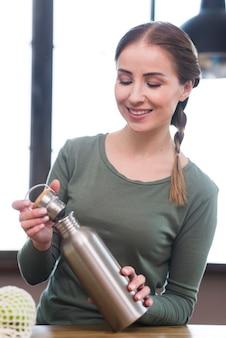 Mooie jonge vrouw met thermoskan