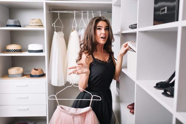 Mooie jonge vrouw met verbaasde blik staande in mooie kledingkast, geïnteresseerd in wat er in de doos zit, roze pluizige rok in handen houden. ze draagt een stijlvolle zwarte jurk.