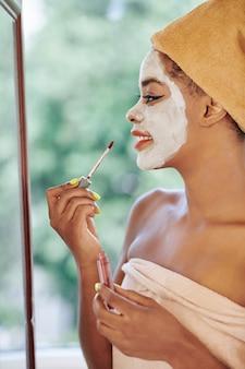 Mooie jonge vrouw met verfrissend kleimasker op haar gezicht die make-up voor spiegel doen na het nemen van een douche