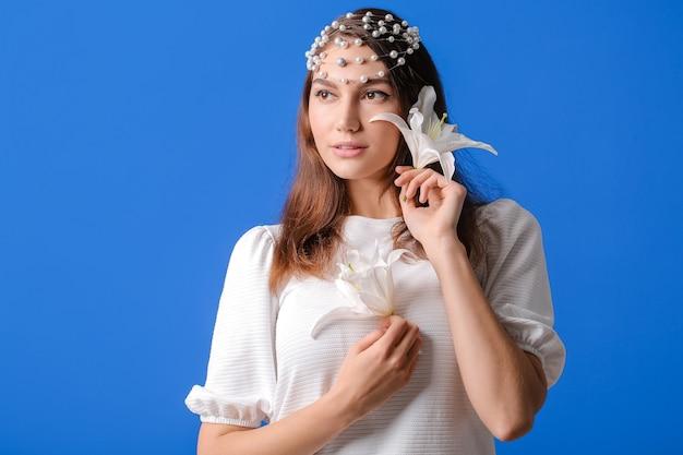 Mooie jonge vrouw met verse lelies op kleur